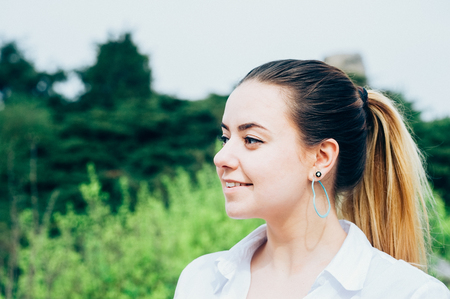 A portrait of a pretty young long haired woman in white shirt, smiling, heart shaped earing, green trees in the background Stock Photo