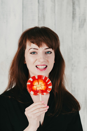 A pretty brunette girl in black dress playfully smiles, holding a red lollipop at her mouth, light wooden background