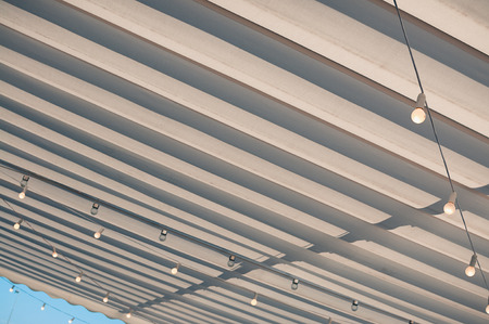 White roofing of a terrace in a street café or restaurant, with bulbs hanging under the awning, in the midday sun against blue sky