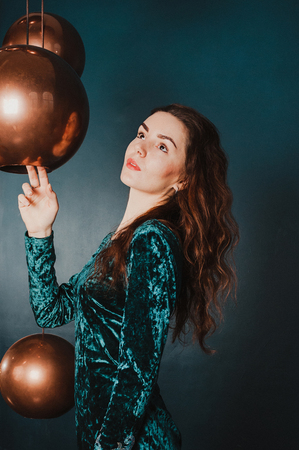 Pretty girl in a green blue velvet dress, playing with hanging big golden balls, dark indigo backdrop. New Year, Christmas holiday concept