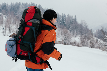 Tourist man walking through snow on winter day, smiling, mountain forest landscape. Blue jeans, orange garment, red backpack. Hiking travel extreme concept. Selective focus