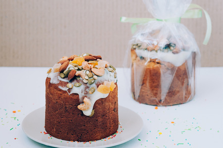 Delicious freshly baked Easter cake with icing, nuts, seeds, candied fruit, multicolored sweet sprinkles, served and packed. Easter, birthday greeting card or web banner concept. Selective focus 版權商用圖片