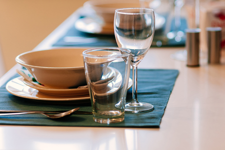 Close up dining setup with empty wine and water glasses, silver cutlery and blue napkins, decorations and items served for food, arranged by catering service in a modern restaurant, cafe