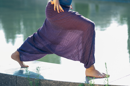 Attractive female practicing yoga asana, wearing baggy cotton trousers of purple color, hands on thighs, bare feet, outdoor, water in background. Healthy lifestyle, keep fit, weight loss concept
