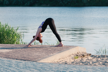 Fit female practice yoga doing stretching exercise pose, outdoor, summer riverside background. Physical and internal healthcare. Healthy lifestyle, keep fit, weight loss, enjoy life and body concept