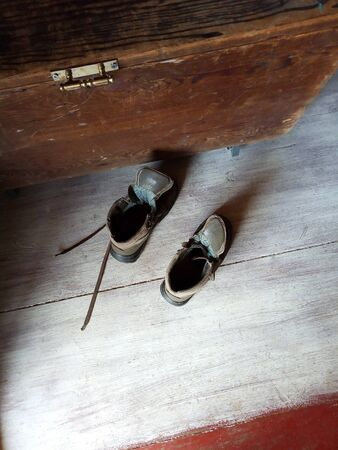 Pair of old brown shoes on wooden floor, shoe retro box next to them. Top view. Natural light