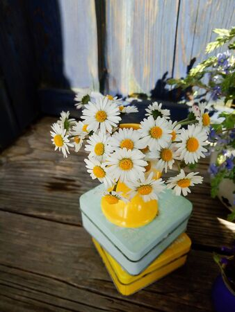 daisy fresh wild flowers in yellow ceramic vase, on wooden veranda background. Still life in rustic style. Close up Top view. Summer in garden, countryside lifestyle concept