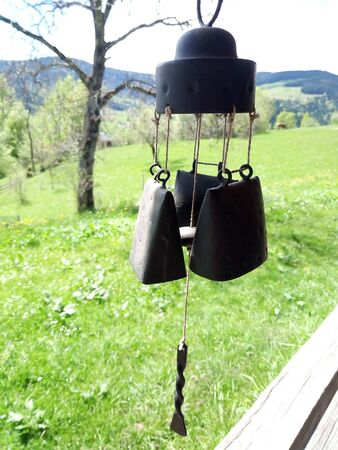 Wind chimes, brass wind bell hanging outside the house against the blue sky, green hill and mountains, in the garden. For home decoration. Music, harmony, meditation concept 스톡 콘텐츠
