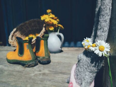 rabbit toy with flowers wreath on head, yellow flowers and rubber gardening ankle boots on wooden veranda background. Still life in rustic style. Daylight, hard shadows. Countryside lifestyle fun concept Reklamní fotografie