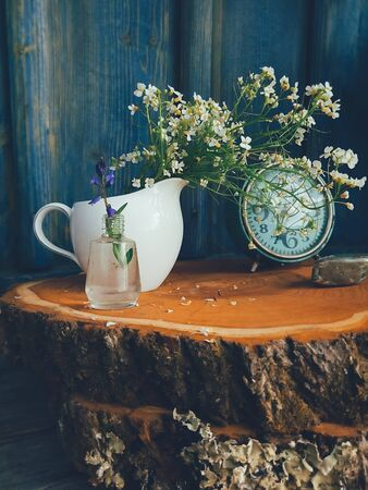 Wild fresh flowers in porcelain jug, old clock on blue wooden background. Daylight, vivid colors. Still life in rustic style. Countryside lifestyle, holiday, vacation concept. Selective focus