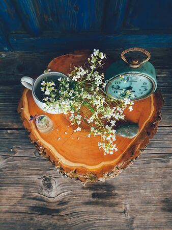 Wild fresh flowers in porcelain jug, old clock on blue wooden background. Daylight, vivid colors. Still life in rustic style. Countryside lifestyle, holiday, vacation concept. Selective focus Top View