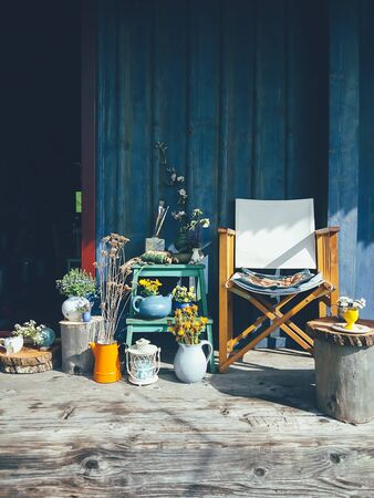 Wild flowers in vases, ceramic jars, pots, a chair, on blue wooden veranda background. Still life in rustic style, daylight. Beauty, Nature, Countryside lifestyle, weekend, vacation, art concept
