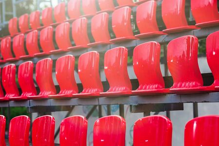 Rows of empty plastic red seats at a small stadium. Outdoors, sunny day. Concert, sports, show concept. Selective focus image