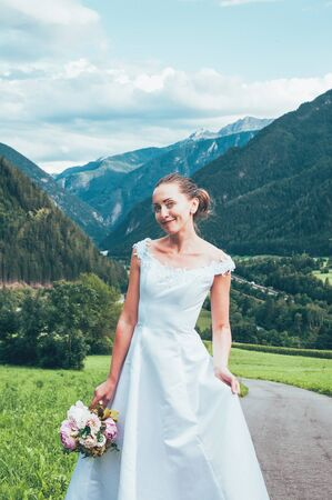 Happy smiling bride in white stylish dress, with a wedding bouquet, beautiful mountains landscape in the background. Summer wedding, honeymoon trip to Italy countryside. Natural makeup, hairstyle