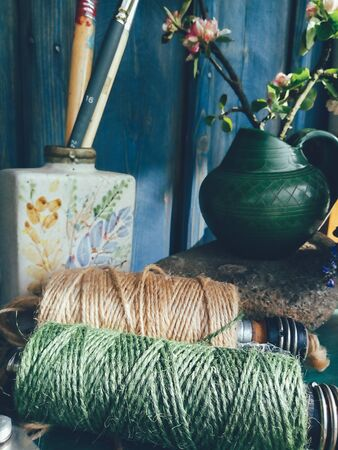 Green string, painter brushes in vase, apple blossom branch, blue wooden background. Still life in rustic style, daylight. Beauty, Nature, Countryside lifestyle, weekend, vacation, art concept