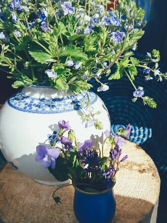 Bouquet of purple field flowers in white porcelain vase, blue round wicker plate and wooden background. Still life in rustic style, daylight. Beauty, Nature, Lifestyle, Art concept
