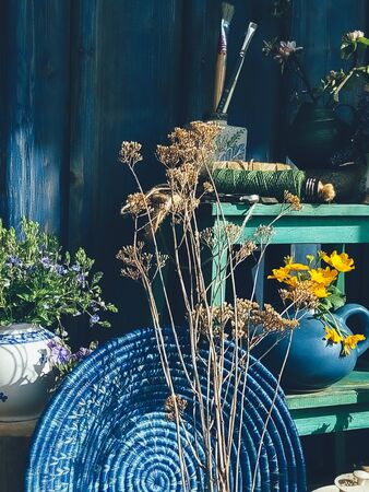 Blue wicker round dish, wild yellow flowers in pot, vase, wooden background. Still life in rustic style, daylight, harsh shadows. Beauty, Nature, Countryside lifestyle, weekend, vacation, art concept
