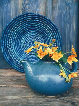 Bouquet of yellow wild flowers in a blue clay pot, on the blue wooden background. Still life in rustic style. Beauty, Nature, Simple. Countryside lifestyle, weekend, vacation, breakfast concept 스톡 콘텐츠