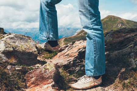 legs of a tourist man standing on the top of Alp mountains, valley beyond the mountain pass,  beautiful landscape. Travel, adventure, freedom, challenge, hiking, vacation concept