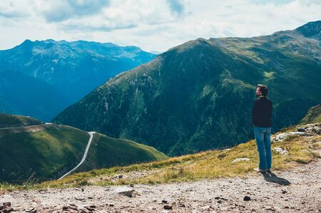 Tourist man standing on the top of Alp mountains, looking at the valley beyond the mountain pass, enjoying the beautiful landscape. Travel, adventure, freedom, challenge, hiking, vacation concept 스톡 콘텐츠