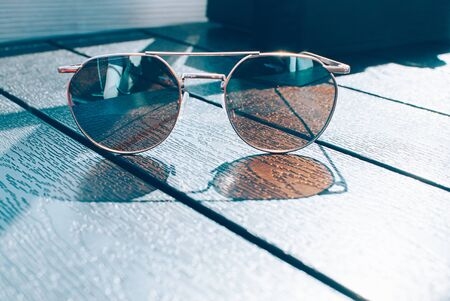 Metal thin trendy sunglasses of brown tint, on wooden table. Sunny day, outdoors, cute reflection and shade. Closeup image, minimal style. Copy space for your text and design. Lounge, travel concept