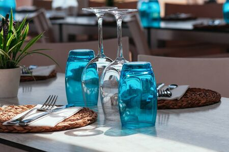 Table setup in restaurant on sunny day outdoor, served for lunch, blue glasses, wicker plates, cutlery. Simple, authentic decor. Beautiful summer holiday concept. Romantic time at resort. Selective focus