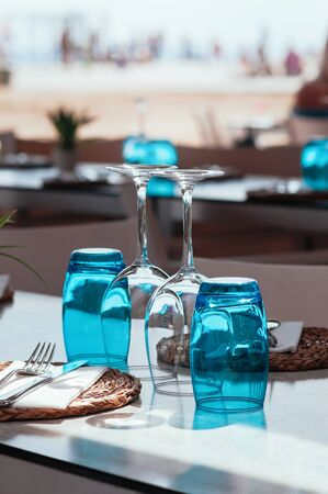 Beach cafe at day light, empty table served for lunch, glasses, wicker plates with cutlery. Simple, authentic decor. Beautiful summer holiday concept. Romantic time at resort. Selective focus