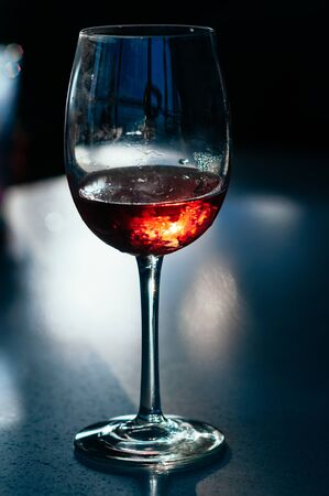 A glass of red wine on the table on dark blue background. Wine in a fogged up glass on a bar table, beautiful flecks and reflections from back light. Party, event, wine tasting, lounge concept 스톡 콘텐츠