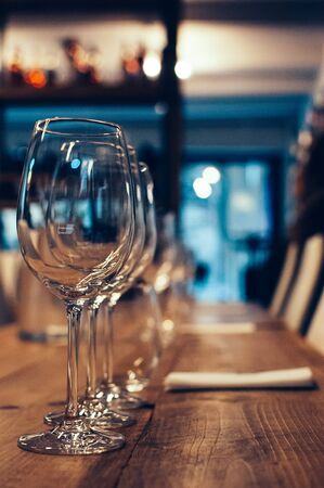 Row of empty wine glasses on a wooden table, served for wine tasting event. Bar or shop interior, subdued light, lovely atmosphere, selective focus, film grain effect 免版税图像