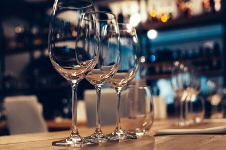 Empty glasses on wooden table, served for wine tasting event. Bar or shop interior, subdued light, lovely atmosphere, selective focus, film grain effect. Bottles on shelves in the background
