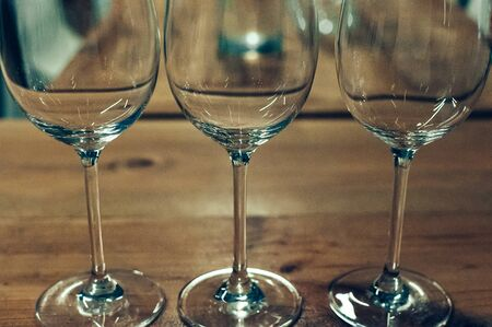 Close up image of three empty glasses with long stalks, on a wooden table, served for wine tasting event. Blurred background. Bar or restaurant interior, subdued light. Selective focus, film grain effect 스톡 콘텐츠