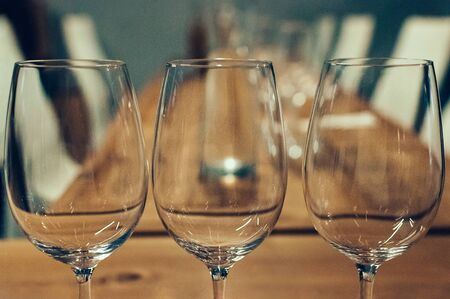 Close up image of three empty glasses on a wooden table, served for wine tasting event. White chairs in the background. Bar or restaurant interior, subdued light. Selective focus, film grain effect
