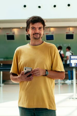 Enjoying travelling. A handsome young man in yellow t-shirt holds a smartphone, standing, looking into camera, smiling. Airport or sea port in the background. Waiting for check in