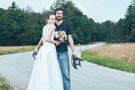 bride in white dress holding flowers, standing on the road, next to handsome man, holding auto jack and wrench, smiling.  An adventurous wedding journey by car, through forest, breakdown and repair 스톡 콘텐츠