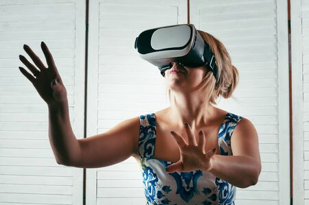 A blonde young woman wearing virtual reality glasses, smiling and pointing her hand in the air, white wooden background 스톡 콘텐츠