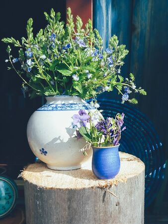 Bouquet of purple field flowers in white porcelain vase, blue round wicker plate and wooden background. Still life in rustic style. Daylight, hard shadows. Minimalism, art concept