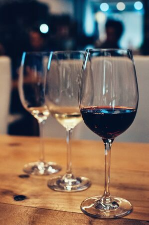 Close up image of three glasses with red and white wine, on wooden table, served for wine tasting event. Blurred background. Bar or restaurant interior, subdued light. Selective focus, film grain effect