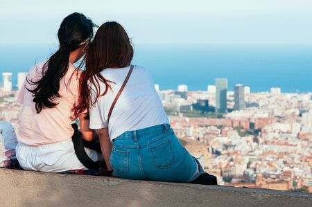 Attractive girls are watching the skyline of Barcelona, sitting on top of Old Bunker hill.  Top view of city streets and harbor. Catalonia, Spain. Enjoy Traveling concept