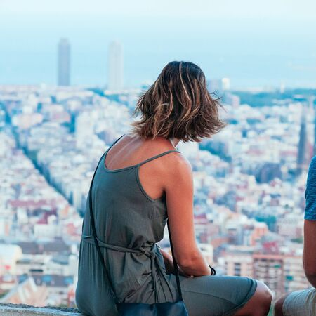 A cute young woman, watching the skyline of Barcelona, sitting on top of Old Bunker hill. Top view of city streets and harbor. Catalonia, Spain. Enjoy Traveling concept