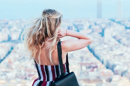 A beautiful young blond woman, watching the skyline of Barcelona, standing on top of Old Bunker hill. Top view of city streets and harbor. Catalonia, Spain. Enjoy Traveling concept