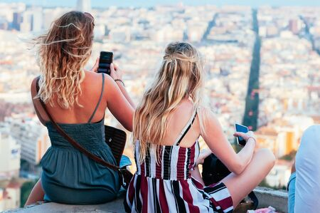 Attractive girls are watching the skyline of Barcelona, sitting on top of Old Bunker hill, taking photos with smart phone. Top view of city streets and harbor. Catalonia, Spain. Enjoy Traveling concept