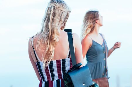 Beautiful female friends, enjoying posing and taking candid photos. Fashion look. Wind through long blond hair. Motion blur, Film Grain effect, Selective focus. Traveling concept. Fun time together 스톡 콘텐츠