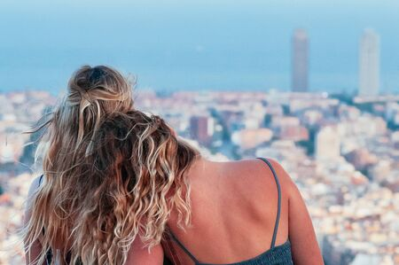 Cute girl friends, enjoying the top view of Barcelona, sitting on top of hill, leaning to each other. Traveling concept. Wind through their long blond hair. Motion blur, Film Grain effect 스톡 콘텐츠