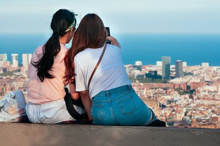 Cute girls, enjoying the skyline of Barcelona, sitting on top of Old Bunker hill, taking photos with smart phone. Top view of streets and harbor. Traveling concept. Motion blur, Film Grain effect 스톡 콘텐츠