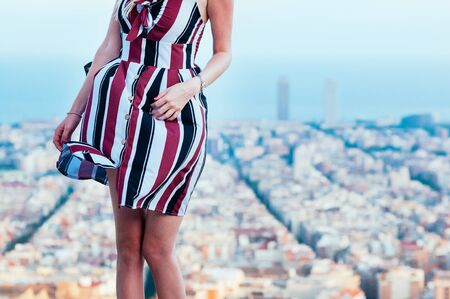 Pretty girl, standing against the blurred top view of Barcelona, enjoys sunset on top of Old Bunker hill. Travel concept. Motion blur, Film Grain effect 스톡 콘텐츠