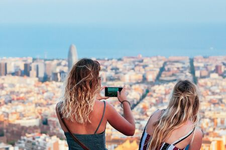 Pretty blond girl friends, standing against the blurred top view of Barcelona, taking photos, enjoying sunset subdued light on top of Old Bunker hill. Travel concept. Motion blur, Film Grain effect
