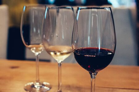 three glasses with red and white wine, on wooden table, served for wine tasting event. Blurred background. Bar or restaurant interior, subdued light. Selective focus. Flm Grain effect