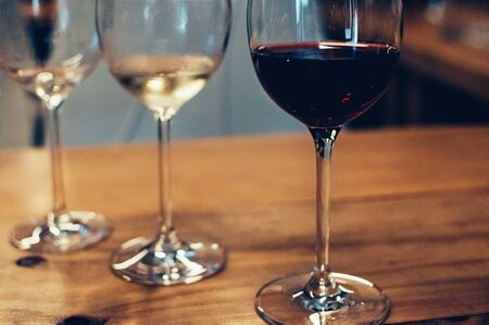 Blurred close up image of glasses with red and white wine, on wooden table, served for wine tasting event. Bar or restaurant interior background, subdued light. Selective shallow focus, film grain effect