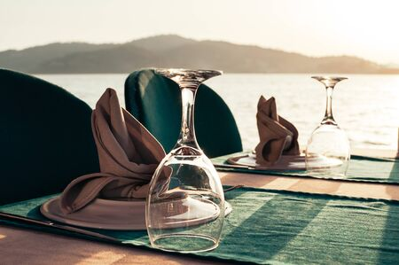 Beach restaurant with sea view at sunset, a table setting served for two. Empty wine glasses, plates on green napkins. Beautiful summer holiday concept. Romantic dinner at resort. Selective focus 스톡 콘텐츠