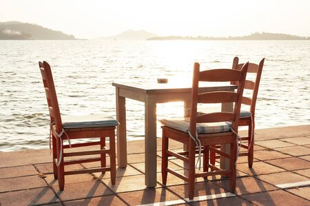 Beach cafe with sea view at sunset, empty table, three chairs, vacant for guests. Simple, authentic wooden furniture. Beautiful summer holiday concept. Horizon with misty mountains on distant island
